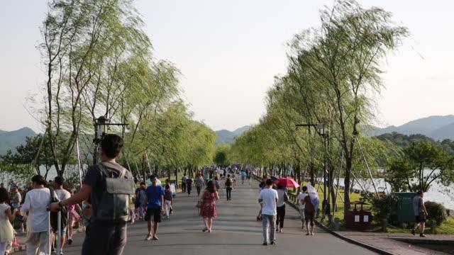 People walking along Bai Causeway on West Lake,Hangzhou,China