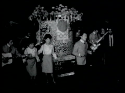 vídeos de stock, filmes e b-roll de night people walking along in city street past neon lit cinema / inside nightclub japanese rock and roll band playing japanese rock and roll club on... - 1964
