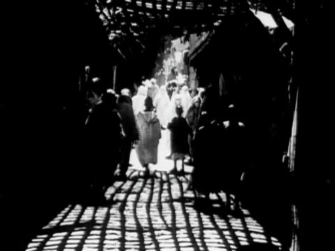 1934 b/w montage ws people walking along narrow shaded souk / rabat, morocco - rabat morocco stock videos & royalty-free footage