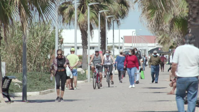 people walking along promenade in the algarve, portugal, as they start to welcome tourists back after coronavirus lockdowns - pedestrian walkway stock videos & royalty-free footage