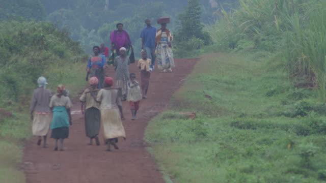 ws people walking along road / buikwe, uganda - ウガンダ点の映像素材/bロール