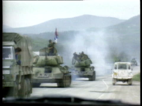 vidéos et rushes de people walking along road, survivors of attack on town, people looking at the damage to their homes / un vehicles and personnel at scene / serb tanks... - bosnie herzégovine