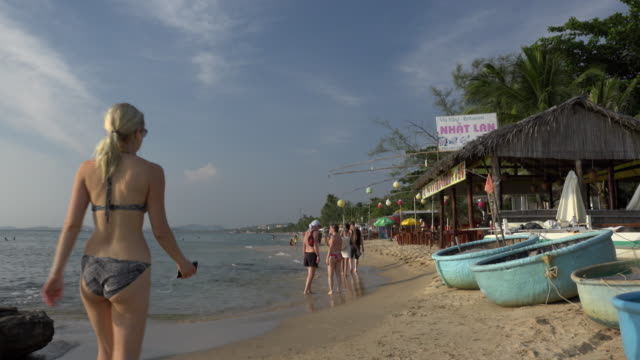 people walking along the beach with coracles and beach restaurant - gulf of thailand stock videos & royalty-free footage
