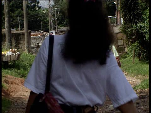 vídeos de stock e filmes b-roll de people walking along track in shanty town sao paulo - favela