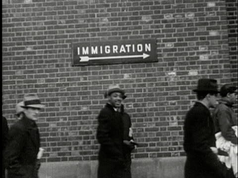 MS, B/W, People walking along wall with sign 'Immigration', USA