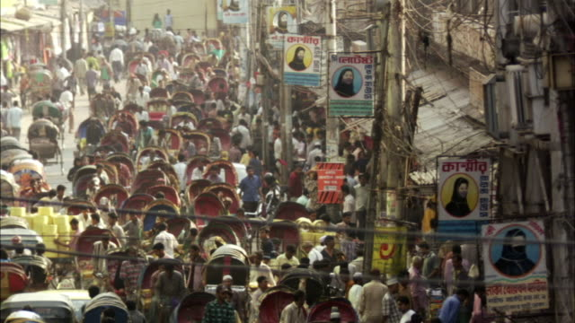 ms, ha, pan, people walking amongst crowd of rickshaws on street , dhaka, bangladesh - dhaka stock-videos und b-roll-filmmaterial