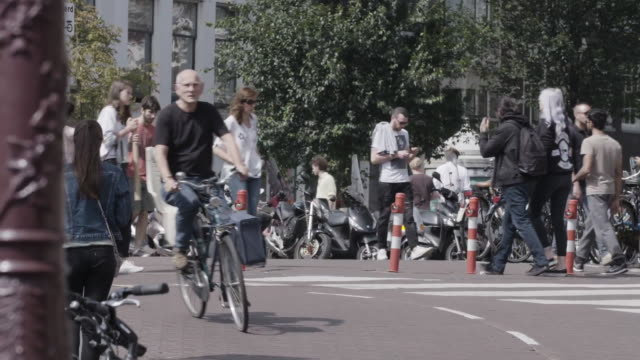 people walking and biking in amsterdam - soleggiato video stock e b–roll