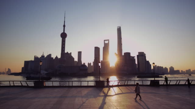 People walking and exercising on the Bund at sunrise