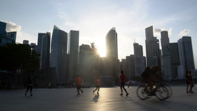 WS People walking and running in front of the Singapore skyline.