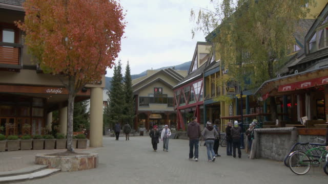 WS ZO People walking and skating through courtyard in Whistler Village / Whistler, British Columbia, Canada