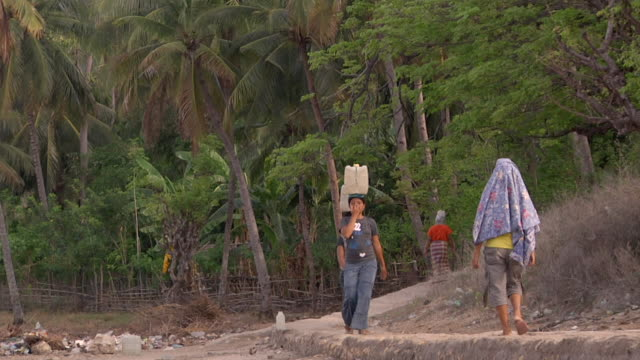 MS People walking and women carrying gallons of water on their heads / Rinca Island, Indonesia