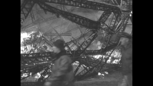people walking around airship hindenburg as it lies on ground burning at naval air station lakehurst / closer shot of people walking around burning... - fire hose stock videos & royalty-free footage