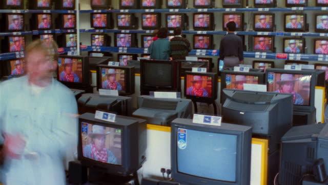 vídeos de stock, filmes e b-roll de t/l, ms, people walking around electronics shop - loja de produtos eletrônicos
