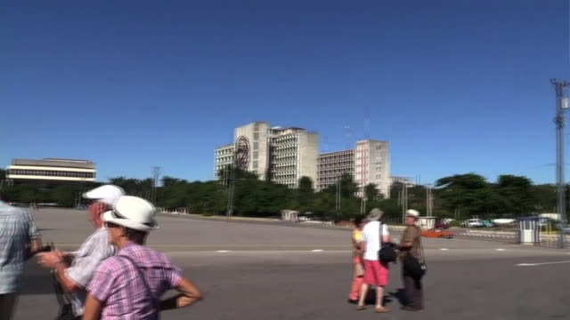 people walking around on the street near the building of ministry of the interior with a 8 storey tall basrelief of ernesto che guevara and a cuban - bas relief stock videos & royalty-free footage