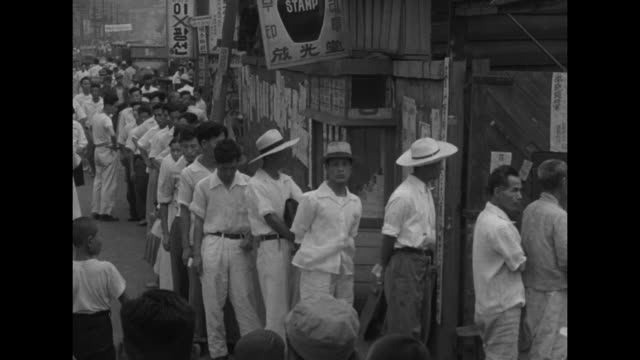 vidéos et rushes de people walking around street in pusan / two shots of people looking at political posters on bulletin board / four shots of people standing line to... - actualités cinématographiques