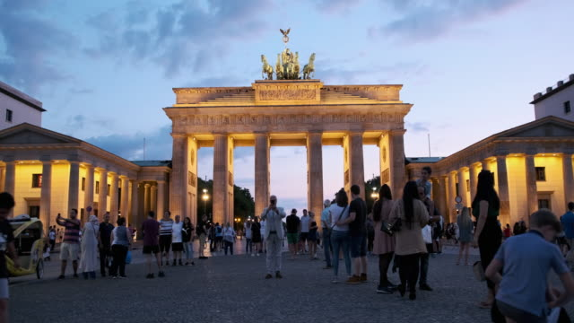 vídeos de stock e filmes b-roll de people walking around the brandenburg gate, germany at sunset - berlim