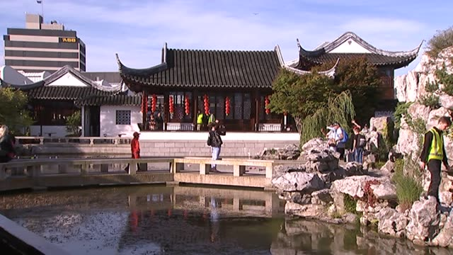 people walking around the dunedin chinese garden during chinese new year celebrations - chinesisches laternenfest stock-videos und b-roll-filmmaterial