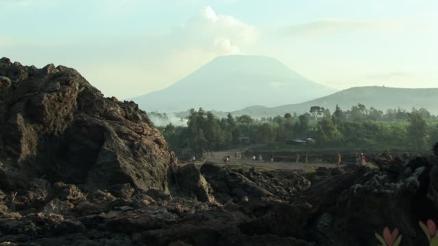 LS WS People walking around valley, volcano in background, Goma, Congo