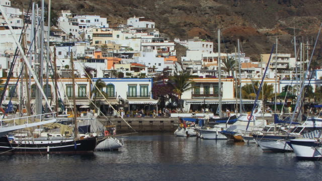 ws people walking around waterfront shopping area behind rows of moored boats/ puerto de mogan, grand canary, canary islands - grand canary stock videos and b-roll footage