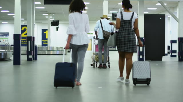 people walking at airport - wheeled luggage stock videos and b-roll footage
