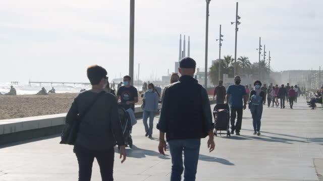 people walking at badalona barcelona promenade during covid-19 crisis - gå tillsammans bildbanksvideor och videomaterial från bakom kulisserna