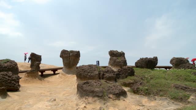people walking at beach with strange shaped rocks in yeliu, taiwan - ロックストラータ点の映像素材/bロール