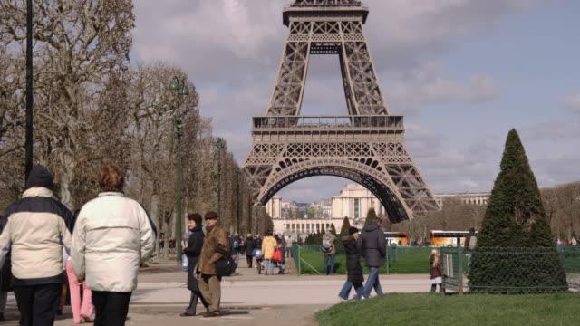 ws people walking at champ de mars, eiffel tower in background / paris, france - エッフェル塔点の映像素材/bロール