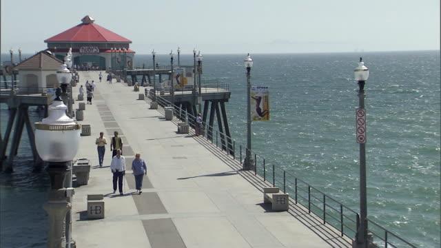 ws people walking at huntington beach, pier and ocean / los angeles, california, usa - huntington beach california stock videos and b-roll footage