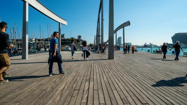 vídeos de stock e filmes b-roll de t/l people walking at port of barcelona, spain - porto de barcelona