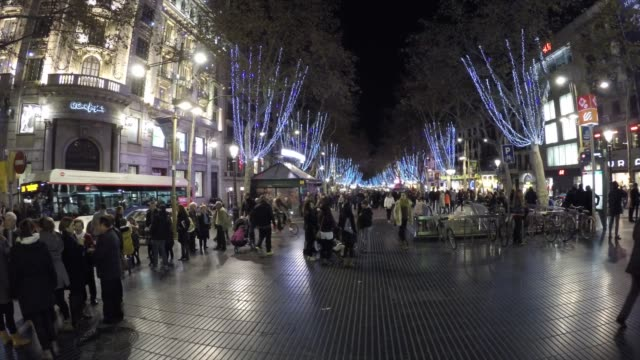 vídeos de stock e filmes b-roll de people walking at the crowded la rambla street at the heart of barcelona, spain - luzes de natal