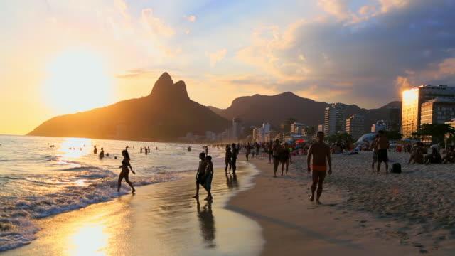 people walking at water's edge - copacabana stock videos & royalty-free footage