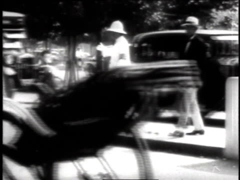 people walking beneath a bridge / busy street with carriages bicycles and vehicles passing a policeman directing traffic / family crossing the street... - 1940~1949年点の映像素材/bロール