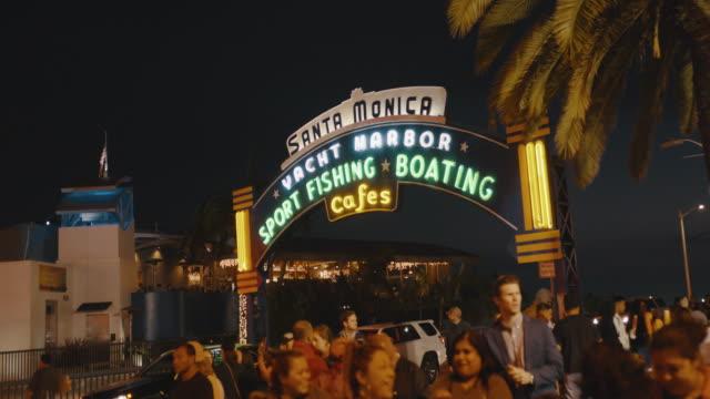 people walking beneath the santa monica pier sign at dusk in los angeles california united states of america - santa monica pier sign stock videos & royalty-free footage