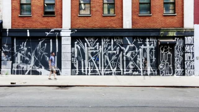People walking by a Graffiti Wall
