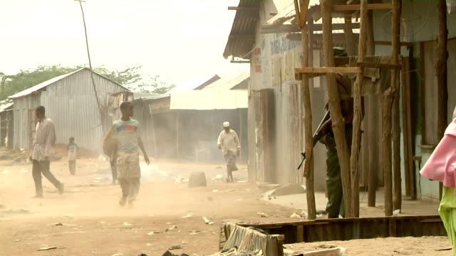 stockvideo's en b-roll-footage met people walking by a windy and smoky area on august 01 2011 in dadaab village kenya - vluchteling ontheemden