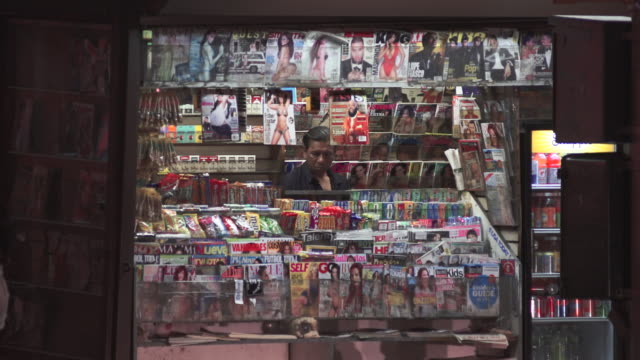 People walking by an attended magazine stand early evening in New York City