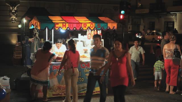 vídeos y material grabado en eventos de stock de ms people walking by food stand at night, merida, yucatan, mexico - mérida méxico