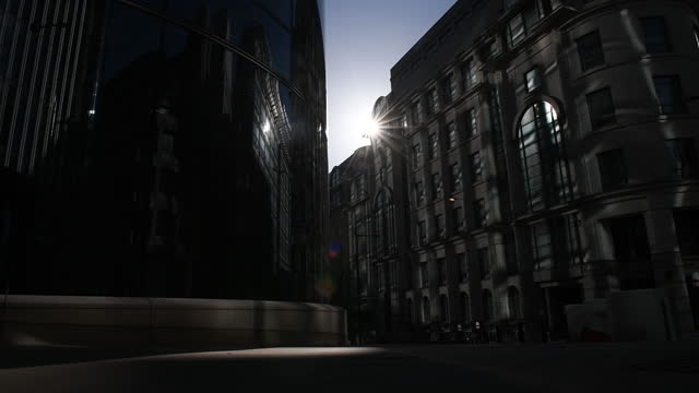 people walking by goldman sachs headquarters as hundreds of bankers return to london offices, in london, u.k. on wednesday, april 7, 2021. hundreds... - lens flare stock videos & royalty-free footage