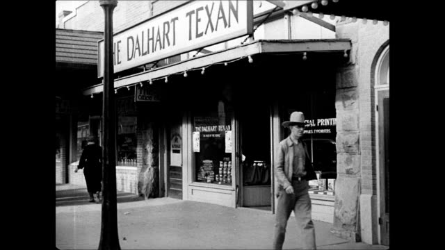 DALHART TEXAS HD People walking by into Dalhart Texan newspaper office Publisher John L McCarty blotting long flyer w/ weight male in cowboy hat...