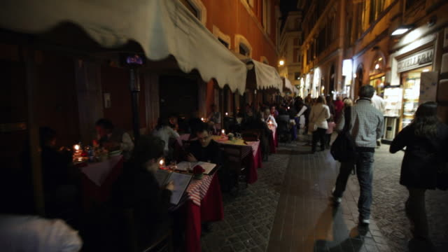 MS POV People walking by people seated at tables outside of restaurant in narrow street  / Rome, Italy