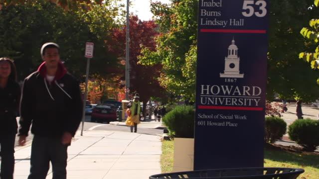 ws people walking by sign saying howard university school of social work / washington, district of columbia, united states - 英字点の映像素材/bロール