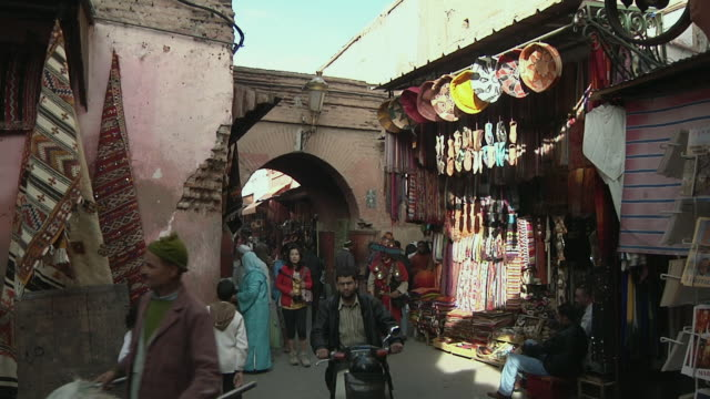 MS People walking by souk market stalls / Marrakech, Morocco