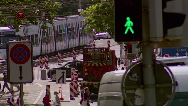 ws td people walking, cars crossing street / zurich, switzerland - trolleybus stock-videos und b-roll-filmmaterial