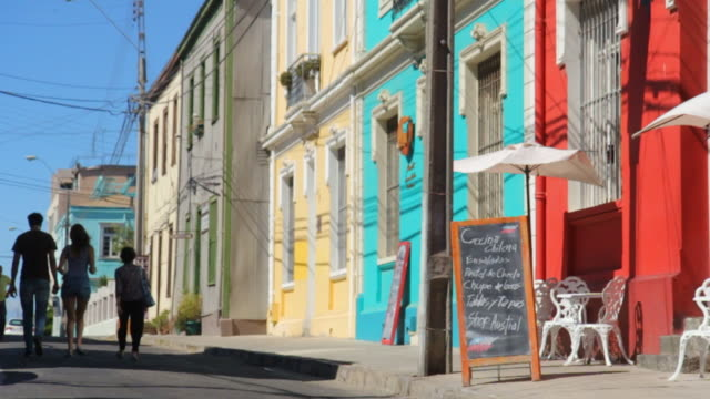 people walking down a street with colorful houses in valparaiso chile - chile stock-videos und b-roll-filmmaterial
