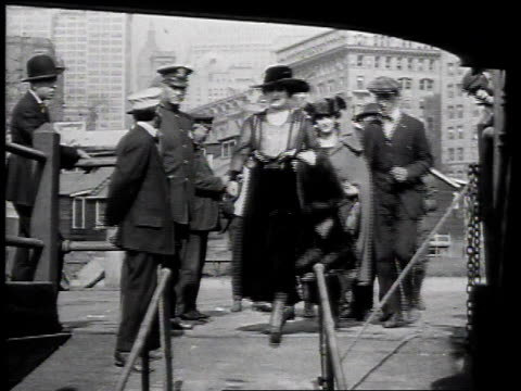 1915 MONTAGE People walking down gangplank onto excursion boat for ride in New York Harbor / New York City, New York, United States