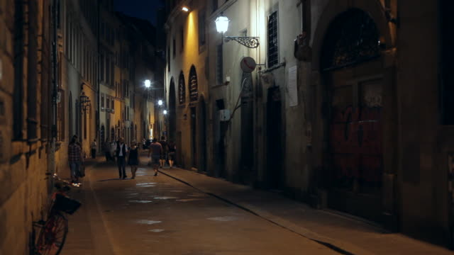 ws ld people walking down narrow street at night / florence, italy - florence italy stock videos & royalty-free footage