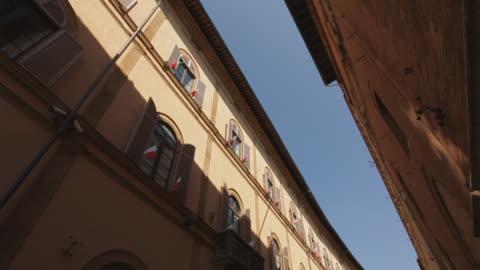 ws td people walking down narrow street between buildings / tuscany, italy - 路地点の映像素材/bロール