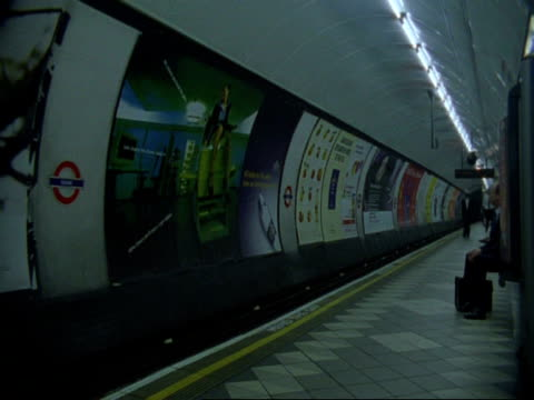 t/l people walking down platform of london underground tube station - poster stock videos & royalty-free footage