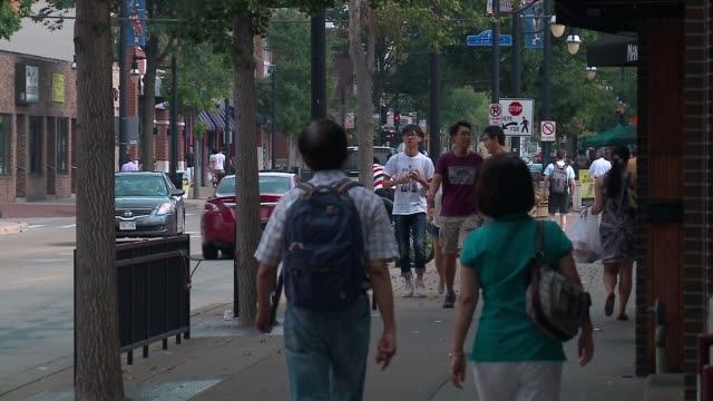 wgn people walking down sidewalks near university of illinois at urbanachampaign - illinois stock-videos und b-roll-filmmaterial