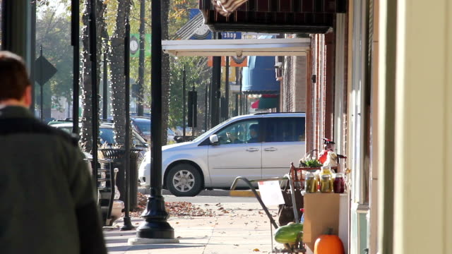 people walking down small town main street - high street stock videos & royalty-free footage